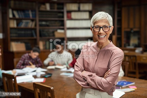 Portrait of mature professor with crossed arms standing in university library and looking at camera with copy space. Happy senior woman at the library working as a librarian. Satisfied college teacher smiling with students in background studying.