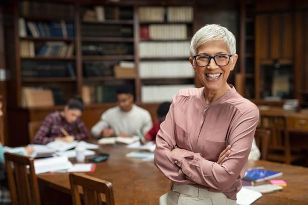 Smiling university professor in library stock photo