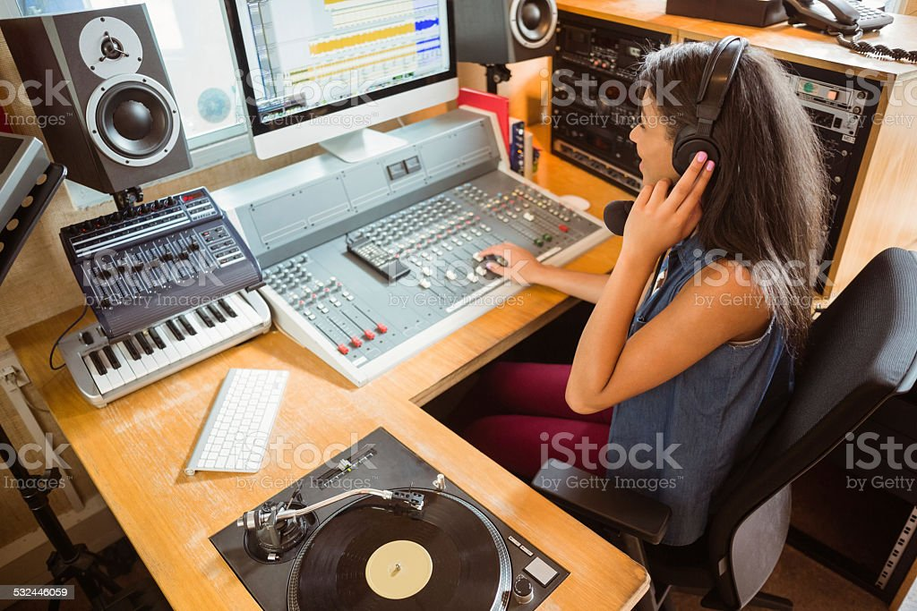 Smiling university student mixing audio stock photo