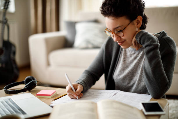 Smiling university student studying at home stock photo