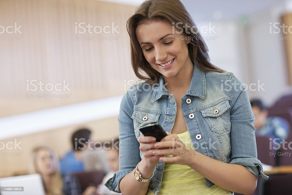 Smiling university student text messaging in lecture hall royalty-free stock photo