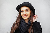 Smiling urban young girl with smile on her face. Portrait of fashionable girl wearing a rock black style and black hat having fun outdoors in the city