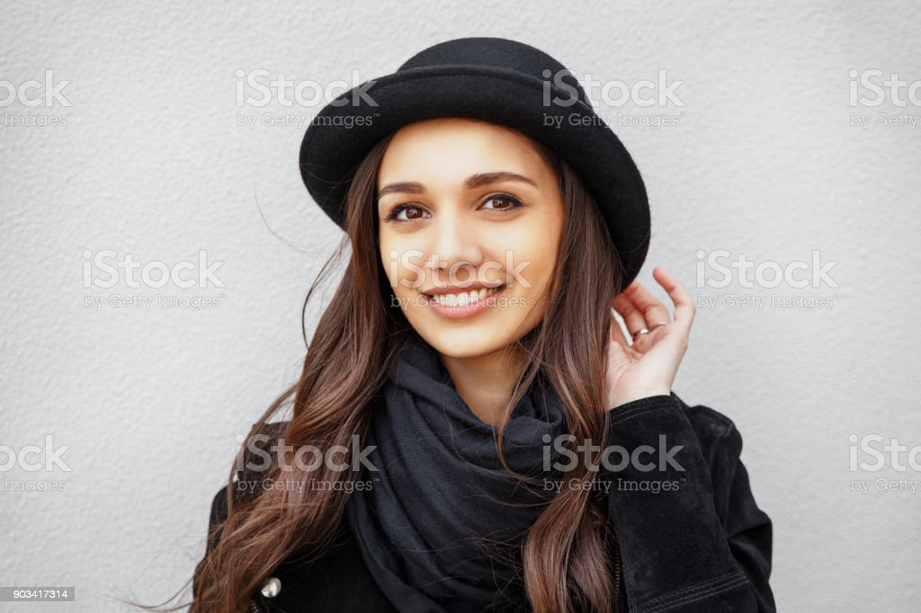 Smiling urban girl with smile on her face. Portrait of fashionable girl wearing a rock black style and black hat having fun outdoors in the city stock photo