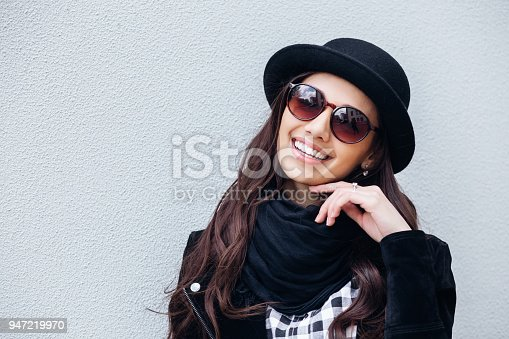 istock Smiling urban girl with smile on her face. Portrait of fashionable girl wearing a rock black style having fun outdoors 947219970