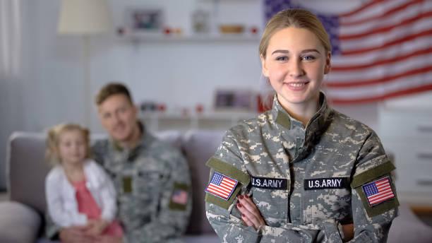 lächelnde us-soldatin, die in die kamera schaut, ehemann und tochter bewundern mama - militäruniform stock-fotos und bilder