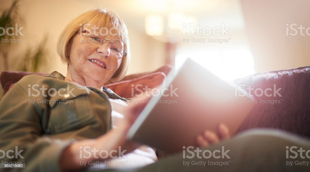 Smiling using digital tablet at home stock photo