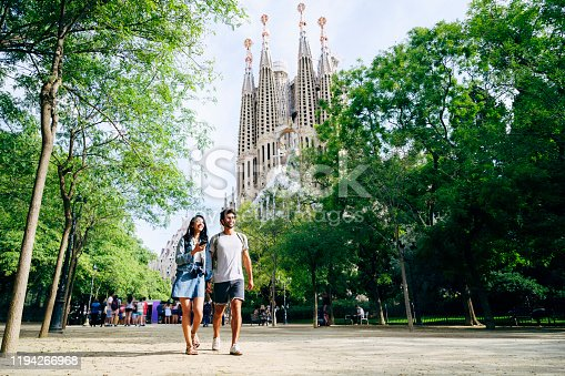 Mid distance low angle view of male and female tourists in 20s and 30s holding hands and walking through Barcelona park near Sagrada Familia.