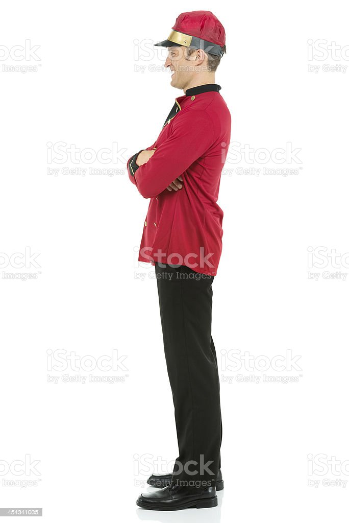 Smiling valet standing with his arms crossed royalty-free stock photo