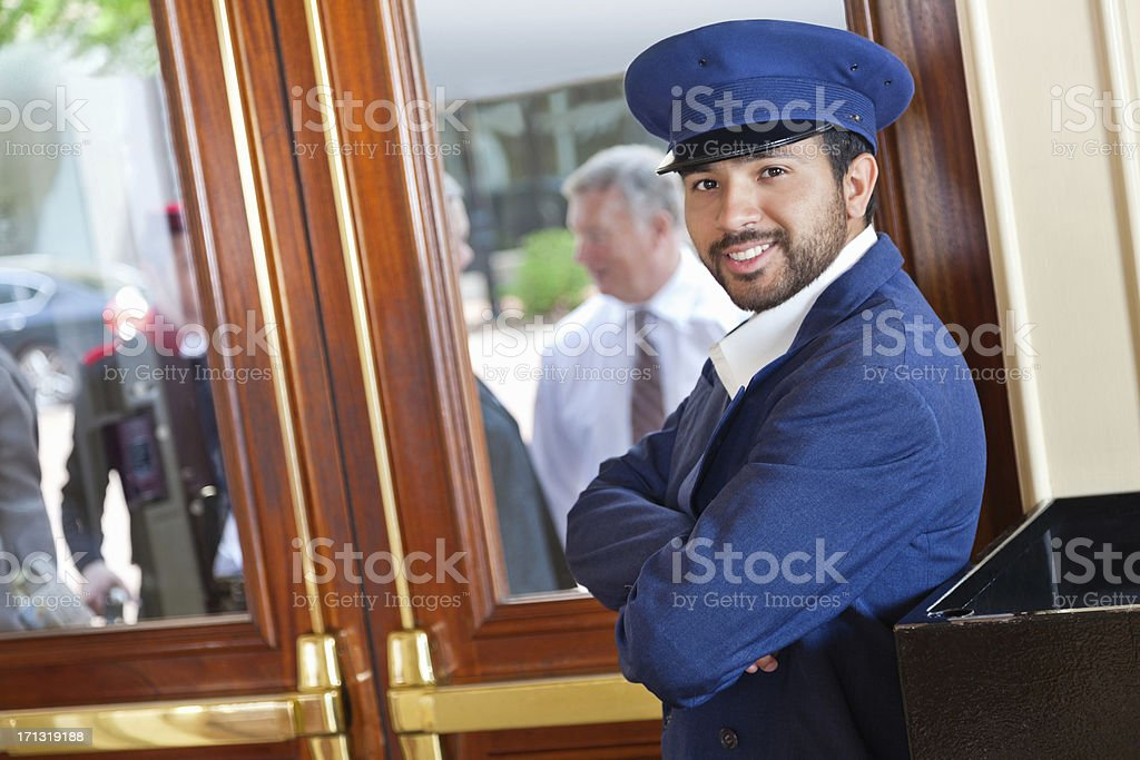 Smiling valet/doorman waiting for guests to arrive at nice hotel stock photo