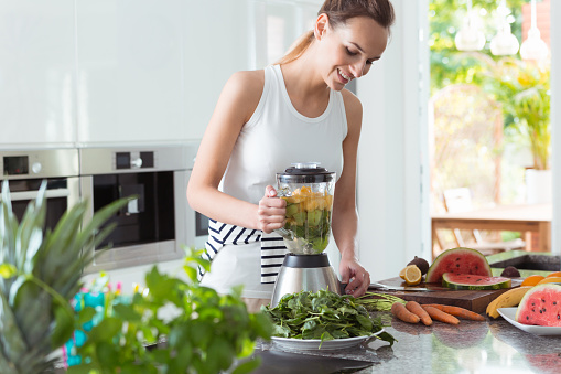 Smiling vegan woman making smoothie with watermelon and carrots