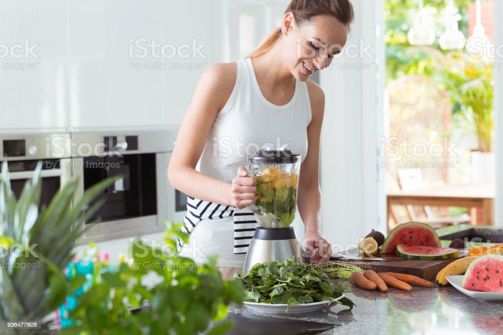 Smiling vegan woman making smoothie stock photo
