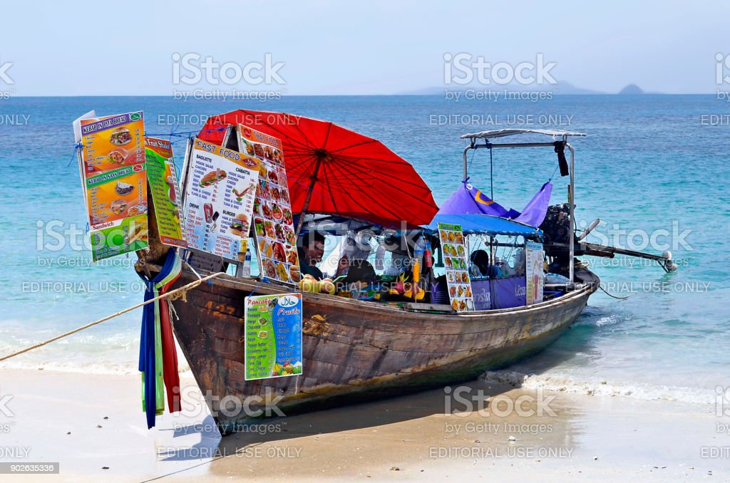 Smiling vendor in a longtail boat selling Thai food on Ao Phra Nang beach stock photo