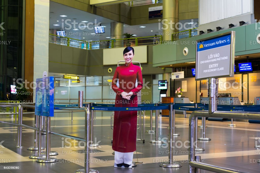 Hanoi, Vietnam - Nov 27, 2014: Smiling Vietnamese woman, the symbol of Vietnam airlines. The photo paper placed at Noi Bai airport stock photo