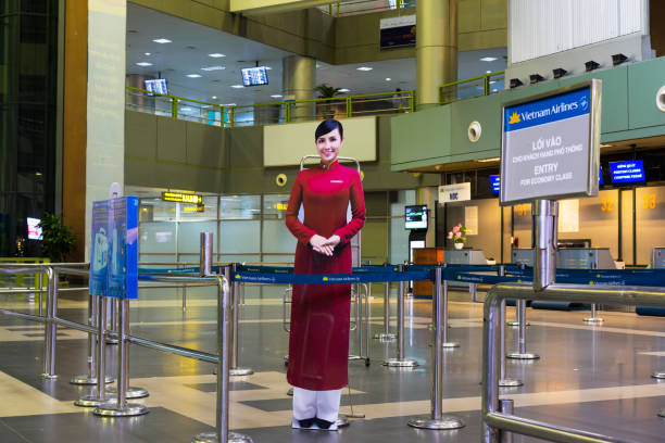 Hanoi, Vietnam - Nov 27, 2014: Smiling Vietnamese woman, the symbol of Vietnam airlines. The photo paper placed at Noi Bai airport stock photo