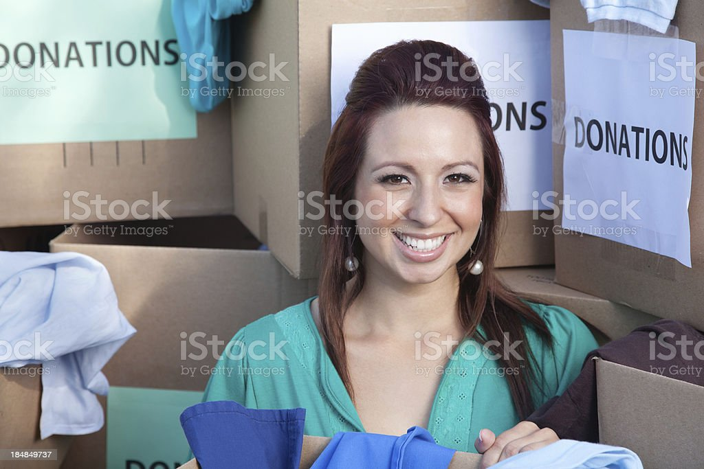 Smiling Volunteer in the middle of donations boxes royalty-free stock photo