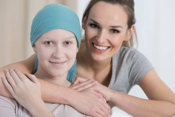 Smiling volunteer supporting patient Portrait of girl with cancer and smiling volunteer supporting patient during therapy chemotherapy cancer stock pictures, royalty-free photos & images