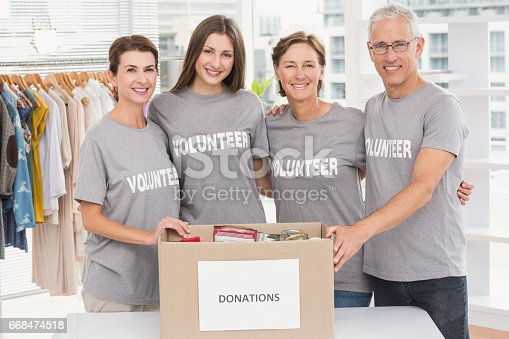 istock Smiling volunteers putting arms around each other 668474518