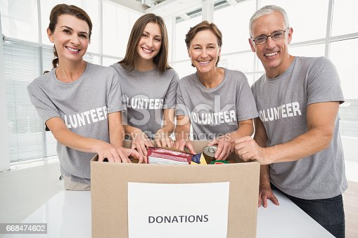 919520858 istock photo Smiling volunteers sorting donation box 668474602