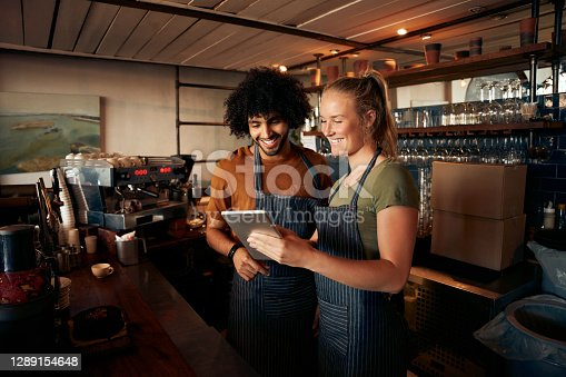 Smiling waiter and waitress using digital tablet standing behind counter in cafe
