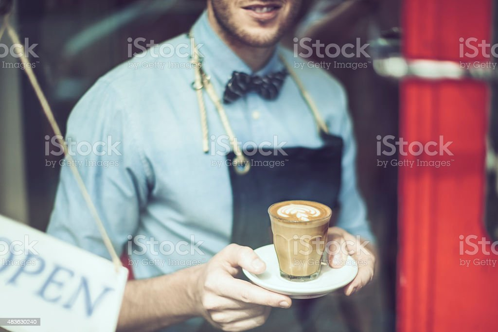 Smiling waiter is holding an espresso royalty-free stock photo
