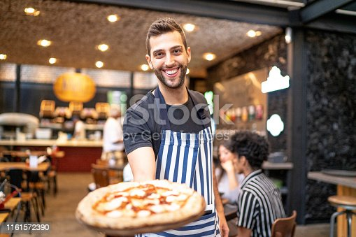 Smiling waiter looking at camera and showing a pizza