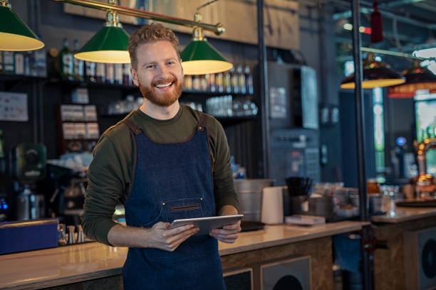 Lächelnder Kellner bereit, in der Kneipe zu bestellen – Foto