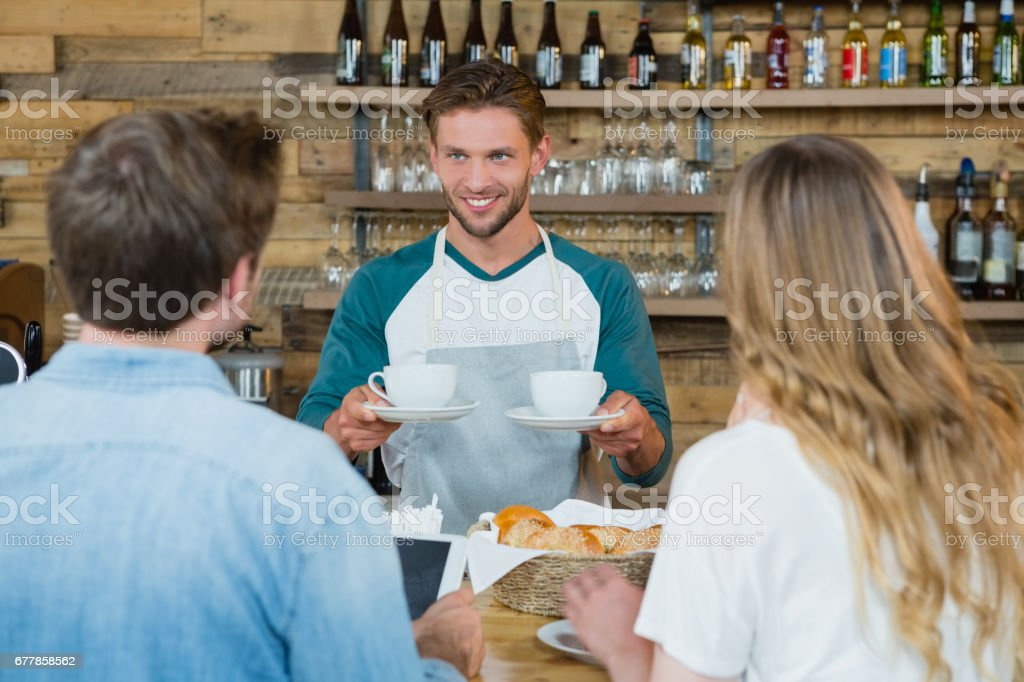 Smiling waiter serving cup of coffee to customers at counter royalty-free stock photo