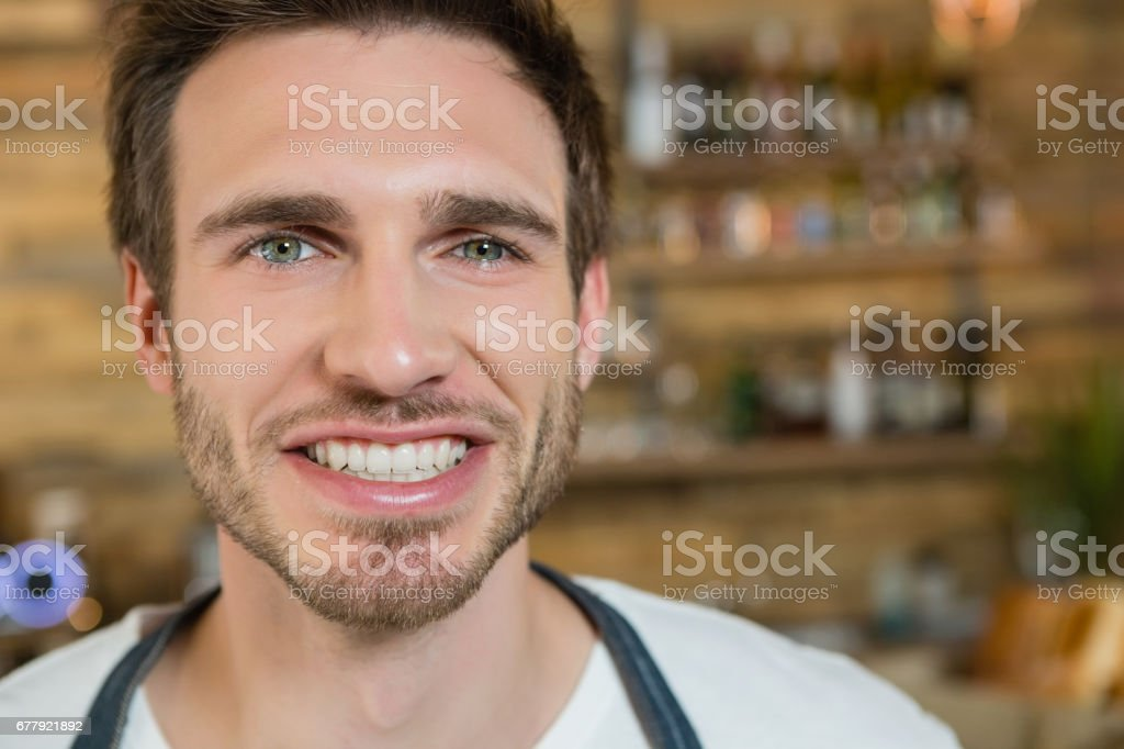 Smiling waiter standing behind the counter royalty-free stock photo