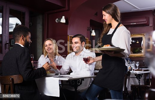 istock Smiling waitress and guests at the table 539236970