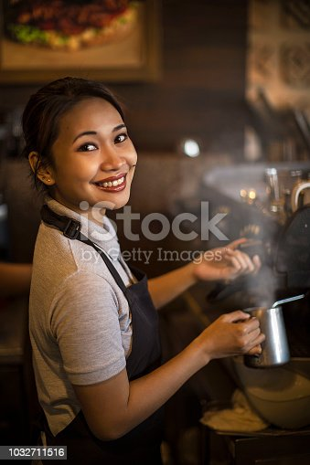 smiling waitress at work steam milk , brew up coffee in cafe shop