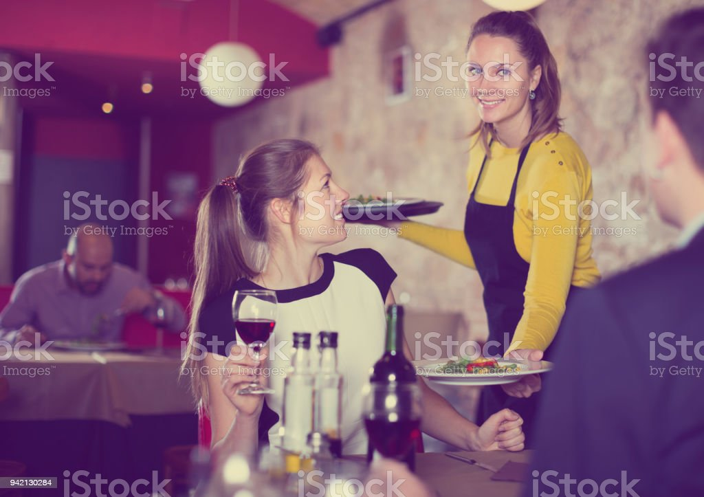 Smiling waitress bringing delicious salads to young people stock photo