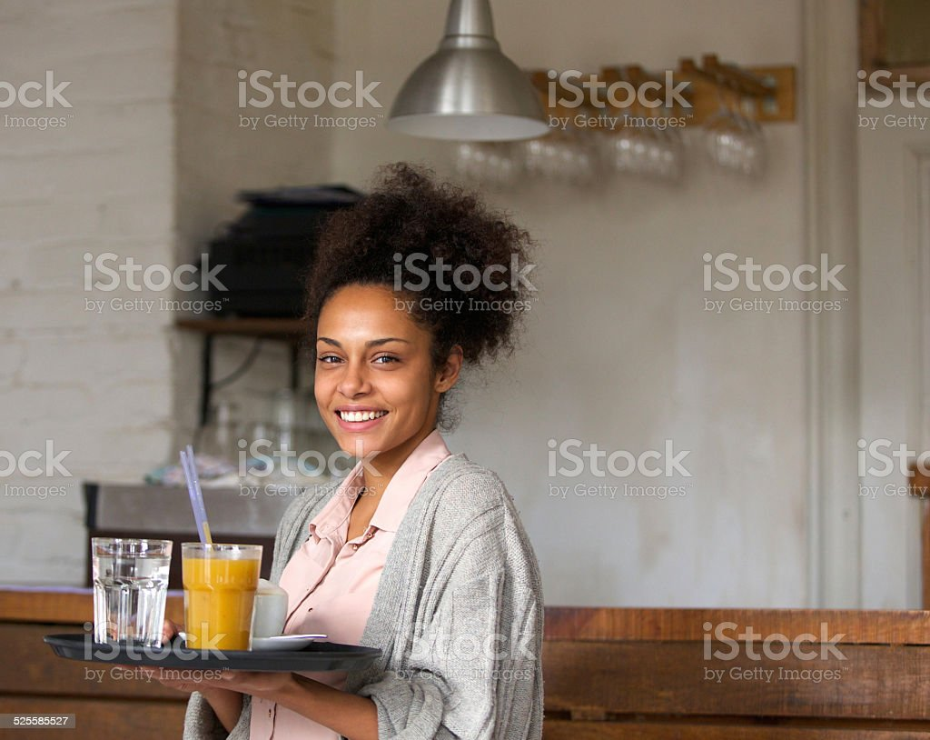 Smiling waitress holding tray of drinks in restaurant stock photo