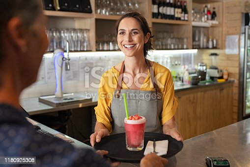 istock Smiling waitress serving strawberry smoothie 1180925308