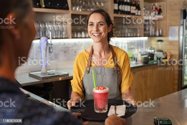Smiling waitress serving strawberry smoothie picture id1180925308?b=1&k=6&m=1180925308&s=612x612&h=6wdvaf6ki7nmnz2u4ogdu00w2t6fvcotjxsgg66cwbk=