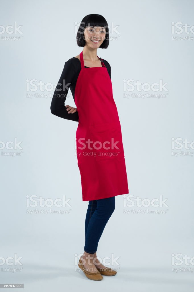 Smiling waitress standing against white background stock photo