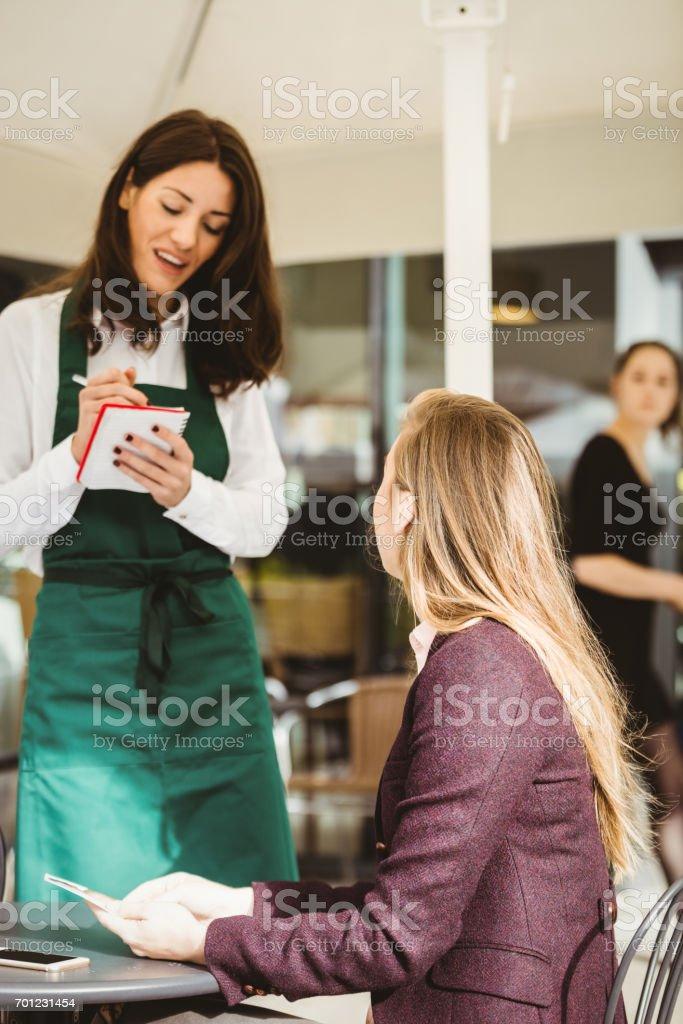Smiling waitress taking an order stock photo