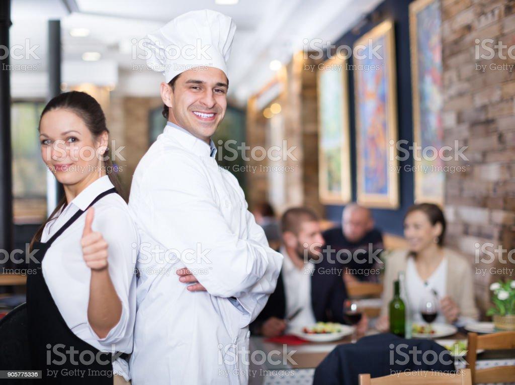 Empregada de mesa com o chef no restaurante a sorrir - foto de acervo