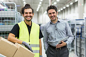 Smiling warehouse worker with foreman