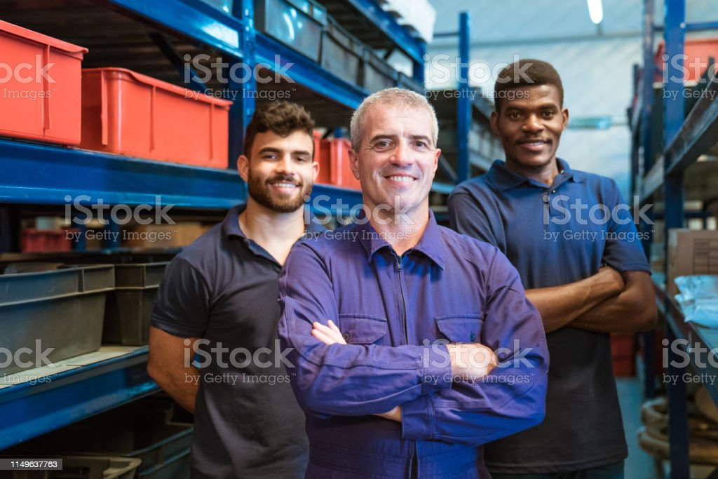 Smiling warehouse workers standing in storage room Portrait of smiling workers standing in storage room. Colleagues are wearing uniform. They are in distribution warehouse. 20-24 Years Stock Photo