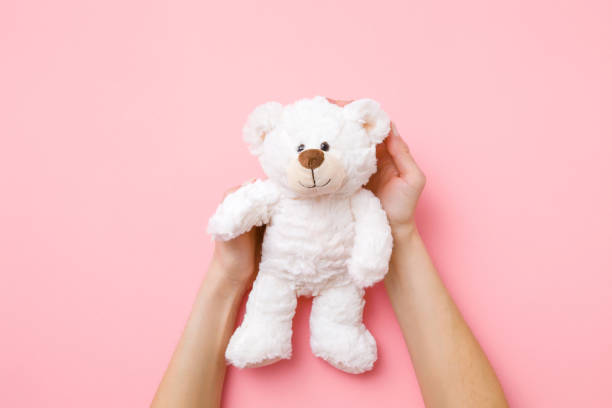 Smiling white teddy bear in girl hands on pastel pink background. Kids best friend. Point of view shot. Top view. Smiling white teddy bear in girl hands on pastel pink background. Kids best friend. Point of view shot. Top view. sentimentality stock pictures, royalty-free photos & images