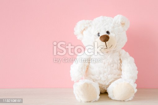 Smiling white teddy bear sitting on table at pastel pink wall background. Kids best friend. Mock up for happy, positive idea. Empty place for emotional, sentimental, lovely text, quote or sayings.