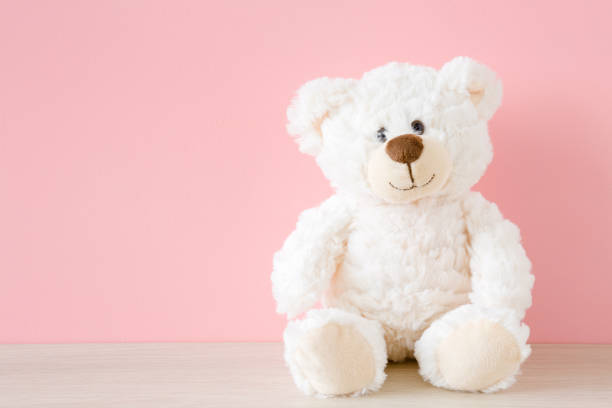 Smiling white teddy bear sitting on table at pastel pink wall background. Kids best friend. Mock up for happy, positive idea. Empty place for emotional, sentimental, lovely text, quote or sayings. Smiling white teddy bear sitting on table at pastel pink wall background. Kids best friend. Mock up for happy, positive idea. Empty place for emotional, sentimental, lovely text, quote or sayings. sentimentality stock pictures, royalty-free photos & images