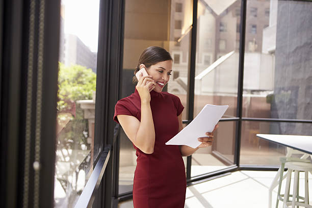 smiling white woman on phone in office looking at document - enge kleider stock-fotos und bilder