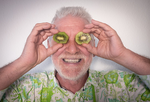 A smiling white-haired senior man with a green kiwi cut in half and placed in front of his eyes