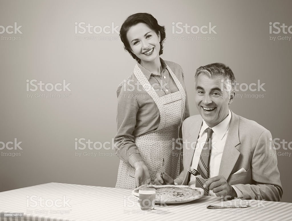 Smiling wife serving dinner stock photo