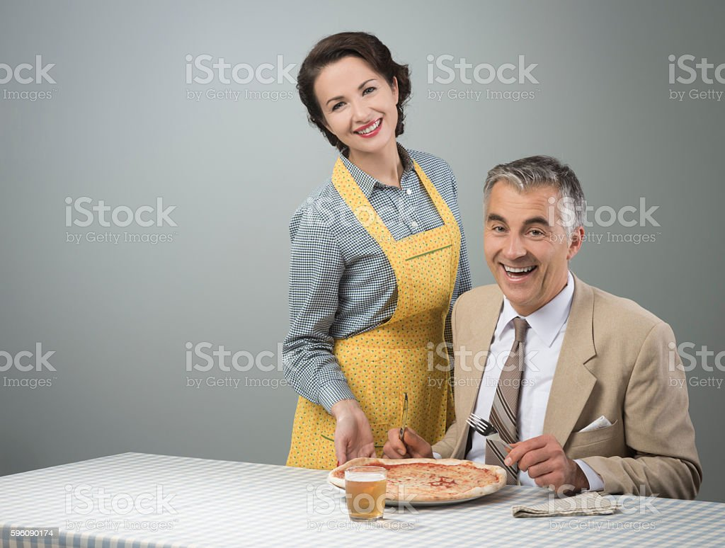 Smiling wife serving dinner royalty-free stock photo