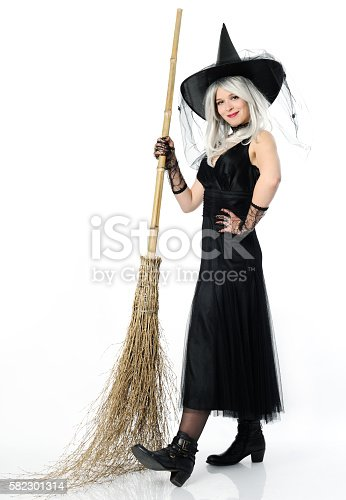 istock smiling witch with broom 582301314