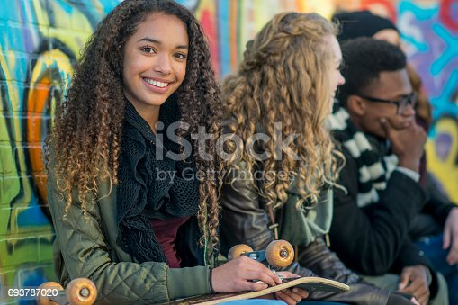 A multi-ethnic group of teenagers are sitting against a wall covered in graffiti. A female of African descent looks away from her friends and smiles as she holds a skateboard.