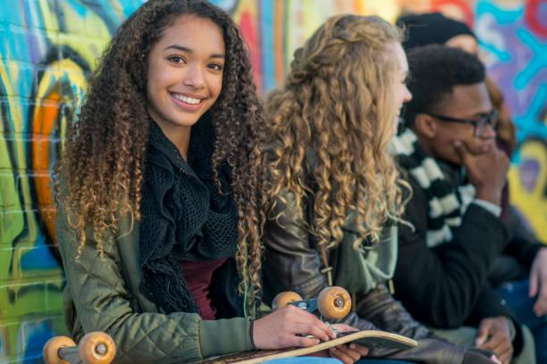 lächelnd mit ihrem skateboard - high school bilder stock-fotos und bilder