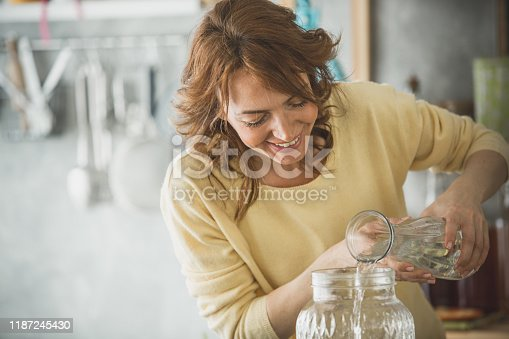 Shot of cheerful mid adult woman pouring water to a big glass container with refreshing lemonade in it that she is preparing.
